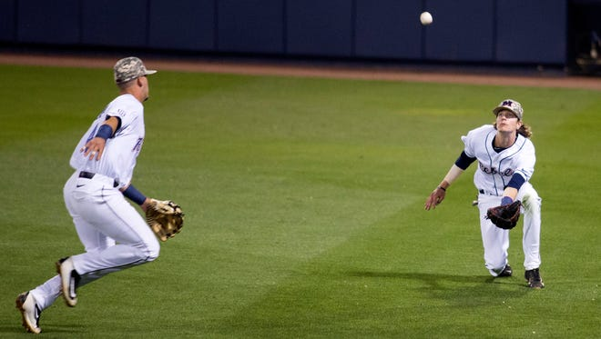 Right fielder Ryan Olenek (right) makes a sliding catch with second baseman Tate Blackman (left) looking on. Olenek, a freshman, came to Ole Miss as a shortstop but transitioned after just one practice.