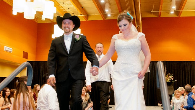 Mr. and Mrs. Garrett Arnold leave the runway of the Las Cruces Bridal Showcase Sunday afternoon after the couple were married moments earlier.Gary Mook/ for the Las Cruces Sun-News