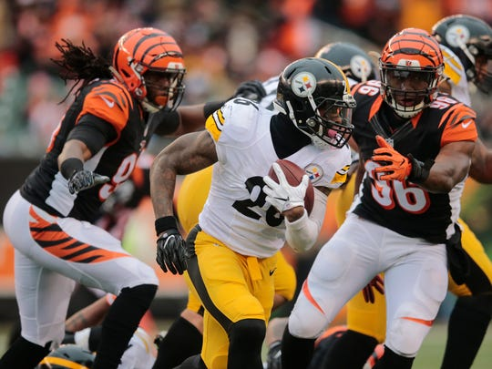 Pittsburgh Steelers running back Le'Veon Bell (26) carries the ball as Cincinnati Bengals defensive end Carlos Dunlap (96) gives chase in the third quarter during the Week 15 NFL game between the Pittsburgh Steelers and the Cincinnati Bengals, Sunday, Dec. 18, 2016, at Paul Brown Stadium in Cincinnati.