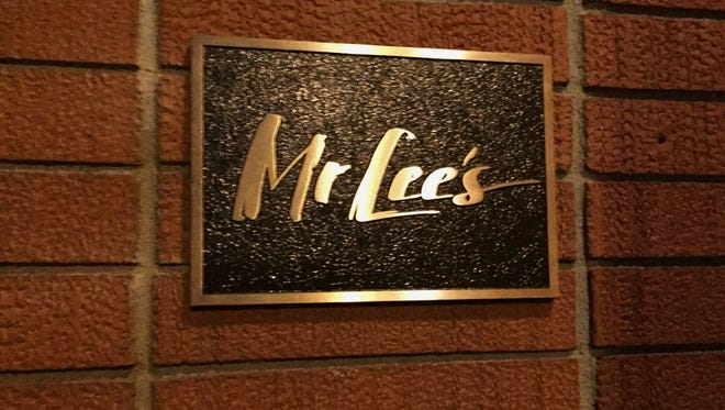 A plaque displays the name of a cocktail bar in Germantown, Mr. Lee's.