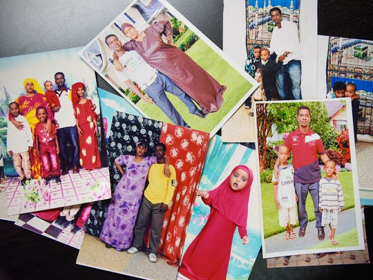 Abdikarim Osman Omar shows his collection of photos of his family Friday, July 6, from visits home to Kenya. He is having trouble getting them to the United State because of the national travel ban.