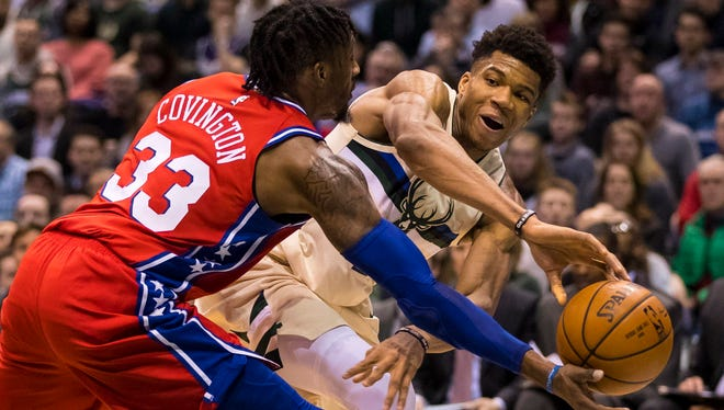 Bucks forward Giannis Antetokounmpo attempts a pass around 76ers forward Robert Covington on Monday night at BMO Harris Bradley Center.