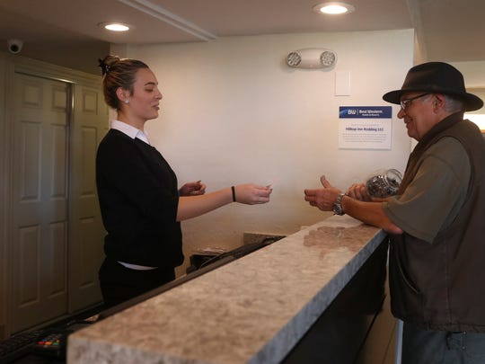 Best Western Plus front desk clerk Megan Potterman, left, helps Ted Bivens, a guest of the hotel last November.