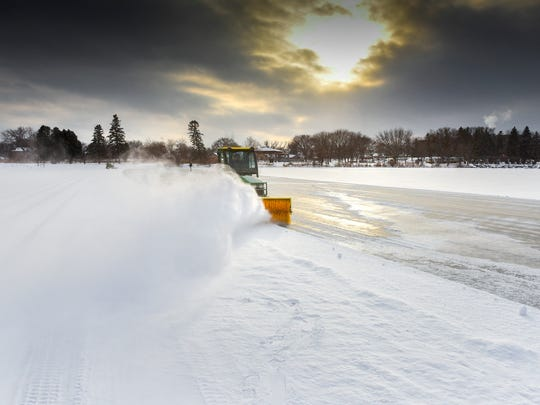 A crew from the St. Cloud Parks & Recreation Department starts clearing the fresh snow off Lake George on Thursday, Dec. 28, 2017.