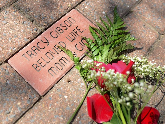 Roses lay on the newly installed brick that have been