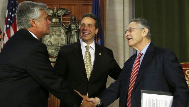 Former Senate Majority Leader Dean Skelos, left, New York Gov. Andrew Cuomo, center, and former Assembly Speaker Sheldon Silver leave a news conference in June 2014. Skelos and Silver face federal corruption charges.