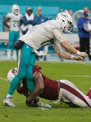 Arizona Cardinals defensive end Calais Campbell (93) tackles Miami Dolphins quarterback Ryan Tannehill (17), during the third quarter of Sunday's game at Hard Rock Stadium. Tannehill was injured on the play.