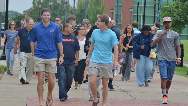 Kyle Elliot, front left, a former Blue Elite tour guide member, leads an MTSU campus tour past the Student Union and near the Student Health, Wellness and Recreation Center in  August 2015.