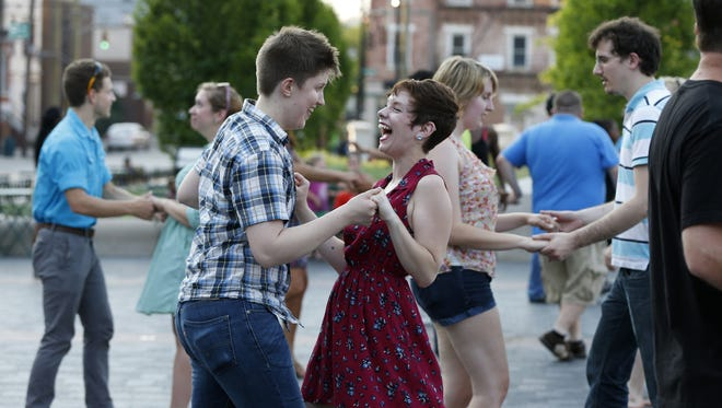 Mary-Clare Quinn of Clifton, left and her dance partner Mia Vera of downtown enjoy their West Coast Swing dance class during the Dance Under the Stars event at Washington Park. This is the one-year anniversary of the reopening of Washington Park downtown in 2013.