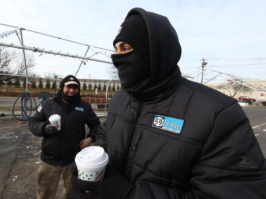 Sotero Figueroa, left, and Marlon Florian bundle up