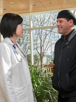 Helen Shih, a radiational oncologist at Massachusetts General Hospital, talks with cancer patient David Fontaine who is in recovery from opioid use disorder.