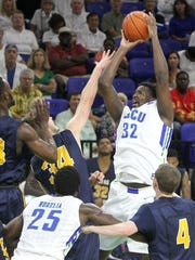 FGCU's Antravious Simmons, right, aims up and over as he is blocked by Wesleyan's Shaun Rost at theTexas Wesleyan vs FGCU home opener Monday in Fort Myers. FGCU won 85-62.
