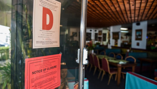 """A """"D"""" rating placard and notice of closure is posted on the entrance door of the Chaopraya restaurant in Tamuning on Saturday, April 28, 2018."""