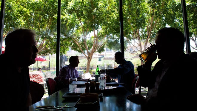 Chris Bowman, front right, takes a sip of his drink while he chats with Frank Cleveringa, front left, while Andrew Sundberg, back left, and Wasim Munawar, back right, enjoy their meal at Olive and Ivy restaurant located at 7135 E. Camelback Rd. in Scottsdale, AZ, on Thursday, June 11, 2015.