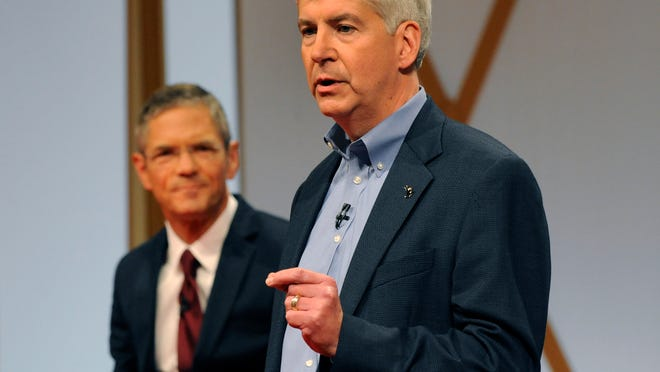 Michigan Governor Rick Snyder, right, addresses the crowd as Democratic challenger Mark Schauer listens during a town hall meeting on the campus of Wayne State University in Detroit, Sunday, Oct. 12, 2014.  (AP Photo/Jose Juarez)