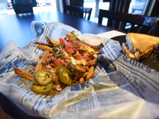The Trash Fries are a popular appetizers at Trotters in downtown New Lexington. At right is the Trotter's Melt.