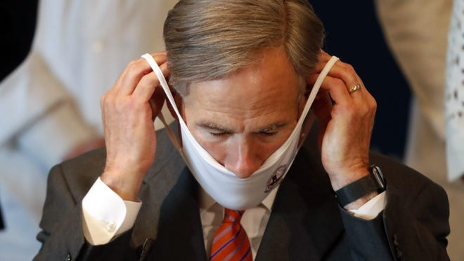 Texas Gov. Greg Abbott puts on a mask to prevent the spread of COVID-19 during a news conference in Dallas on Aug. 6. UT Southwestern Medical Center hosted a round table discussion about preparations for the upcoming flu season amid the ongoing coronavirus pandemic.