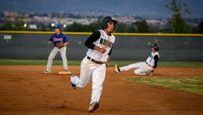 Oñate's Alex Velasco heads towards third as Mikey Avilucea slides into second Tuesday night at the Field of Dreams.