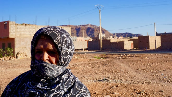 "Rkia Ouabi in her neighborhood in Zagora, Morocco, on the edge of the desert. The inscription on the mountain declares: ""God, Country, King."""