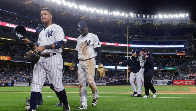 New York Yankees' Starlin Castro, left, and Didi Gregorius, second from left, leave the field as New York Yankees' Chris Parmelee is helped off during the seventh inning of a baseball game against the Los Angeles Angels on Thursday, June 9, 2016, in New York.
