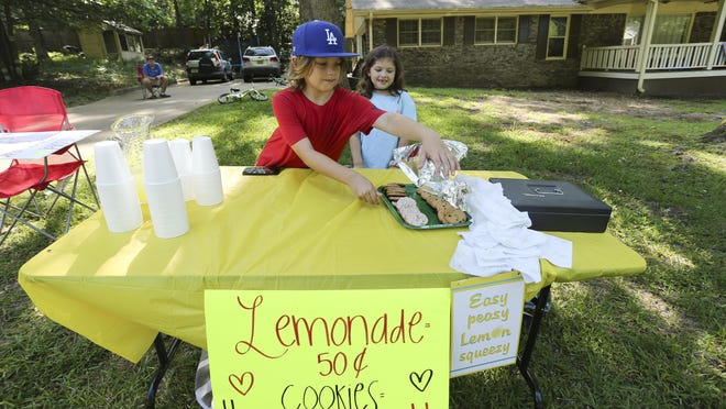 Eric Jones and his sister Shaeleigh sell lemonade and cookies in front of their home in Northport Friday, June 5, 2020. The kids said they are trying to raise some spending money for an upcoming vacation trip.