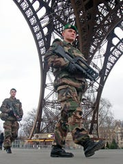 French army soldiers patrol under the Eiffel Tower