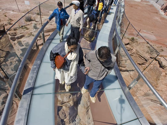 Tourists walk on the glass-bottomed Skywalk that extends
