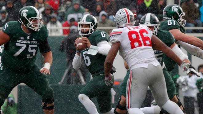 Michigan State quarterback Damion Terry scrambles against Ohio State's Dre'Mont Jones as MSU's Benny McGowan (75), Cole Chewins (61) and Brian Allen block in the fourth quarter Nov. 19, 2016, in East Lansing.