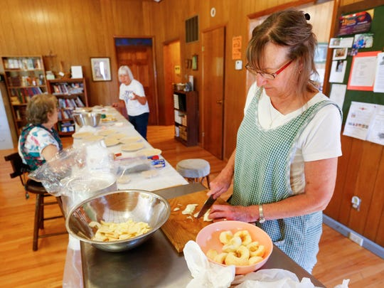 Judy Crockett, right, a member of the Friendship Guild at St. Peter's Evangelical Church in Billings, helps make apple pies for the group's fundraiser.