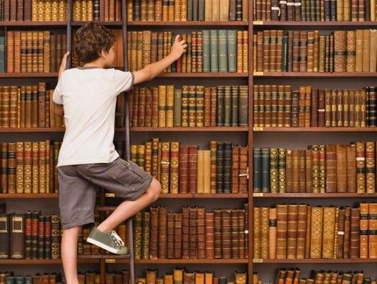 Boy climbing ladder in library