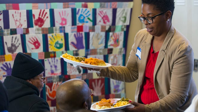 Volunteer Esther Montgomery serves dinner to clients Sunday, Dec. 25, 2017, at Repairers of the Breach, 1335 W. Vliet St., Milwaukee.
