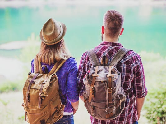 Hipster couple backpacking and enjoying view at the lake