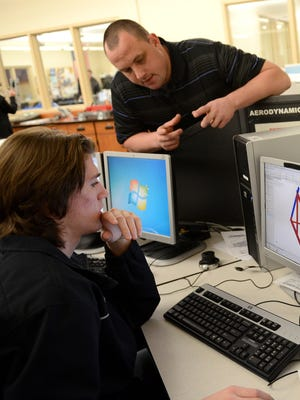 Teacher David Vander Velden works with Trenton LeDocq during engineering class at Bay Port High School. The Upward Together initiative would fund improved labs.