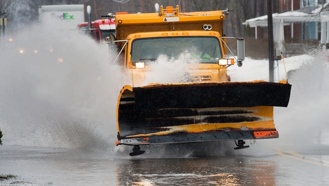 A plow blasts though standing water on the Susquehanna Trail in Manchester Township. Melting snow and heavy rain created some road flooding.