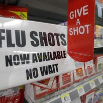 A Walgreen store in Indianapolis tells customers Tuesday they can get flu shots there. The nation's biggest drugstores and retailers are grabbing larger chunks of the immunization market.