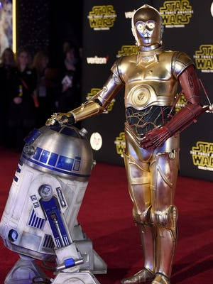 """Film characters R2-D2, left, and C-3PO arrive at the world premiere of """"Star Wars: The Force Awakens"""" at the TCL Chinese Theatre on Monday, Dec. 14, 2015, in Los Angeles. (Photo by Jordan Strauss/Invision/AP)"""