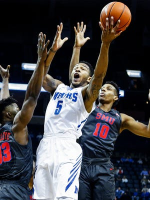 University of Memphis guard Markel Crawford (middle) drives the lane against SMU defenders Semi Ojeleye (left) and Jarrey Foster (right) during first half action at the FedExForum.