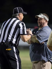 Milton head coach Harry Lees has a chat with a referee during the Gulf Breeze vs Milton high school football game in Milton on Friday, September 29, 2017.
