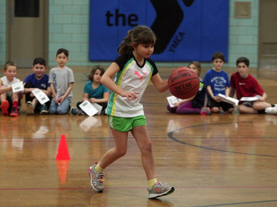 7-year-old Kayla Bhatia of Chatham dribbles the ball as the Madison Area YMCA hosts the NBA's FiT Dribble, Dish & Swish for youngsters.