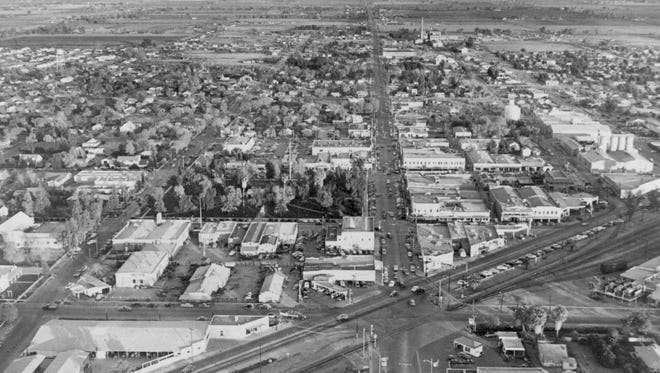 This is downtown Glendale in 1950 looking east along Glendale Avenue at the six-points intersection of Grand, Glendale and Central (59th) avenues. Grand and the Santa Fe railroad tracks cut diagonally across Glendale Avenue. Trees in the center delineate City (Murphy) Park. On the right are the warehouses and silos of Southwest Flour and Feed Company. The large building in the lower left, on Central Avenue, is O'Malley Lumber Company. The buildings in the block west of the park are gone, replaced in the 1980s by the Municipal Office Complex and parking garage.