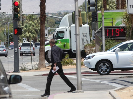 A man crosses the Portola in Palm Desert as a bank display gives a temperature reading of 119 degrees during the noon hour of June 21, 2016.