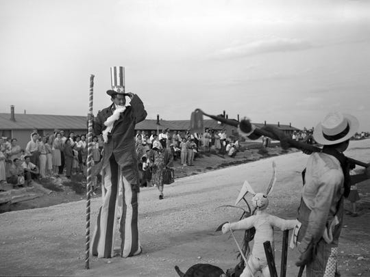 """A marcher in the annual """"Summer Carnival Parade"""" at the Granada camp in Colorado on July 10, 1943. This photo is featured in an exhibit on Japanese internment at the FDR Presidential Library and Museum in Hyde Park."""