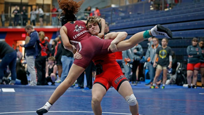 In this Friday, Feb. 16, 2018 photo, Euless Trinity's Mack Beggs, right, takes down Lewisville's Elyse Nelson in the second round of the 110-pound girls division during the 6A Region II wrestling meet at Allen High School in Allen, Texas, Beggs, a senior from Euless Trinity High School near Dallas is transgender and in the process of transitioning from female to male. (Jae S. Lee/The Dallas Morning News via AP)