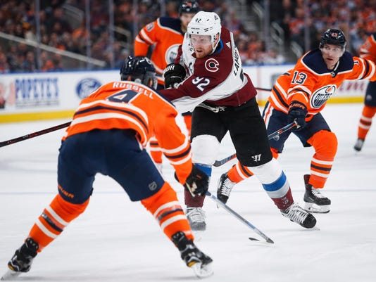 Colorado Avalanche's Gabriel Landeskog, center, of Sweden, fires the puck past Edmonton Oilers' Kris Russell, left, as Michael Cammalleri watches during the first period of an NHL hockey game Thursday, Feb. 22, 2018, in Edmonton, Alberta. (Jeff McIntosh/The Canadian Press via AP)