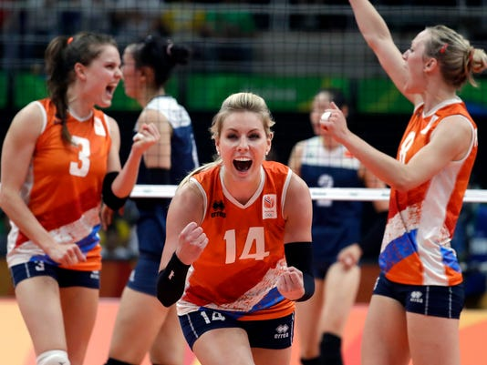The Netherlands' Laura Dijkema (14) celebrates with teammates Yvon Belien (3) and Judith Pietersen, right, during a women's semifinal volleyball match against China at the 2016 Summer Olympics in Rio de Janeiro, Brazil, Thursday, Aug. 18, 2016. (AP Photo/Jeff Roberson)