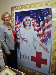 Sarah Tippet Ruwe, executive director of the local Red Cross chapter, stands next to a poster from a century ago featuring a young woman wearing the same uniform her grandmother wore as a Red Cross volunteer.