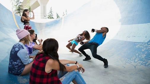 Teenagers dancing at skateboard park