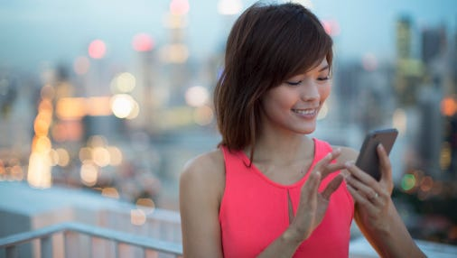 Woman using handphone with city in background.