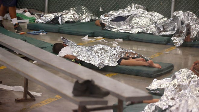 Young boys sleep in a holding cell at U.S. Customs and Border Protection's Nogales Placement Center on June 18, 2014.