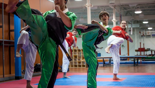 Caitlyn Farenger, 19, and Joey McElwain, 15, practice a form along with other members of Fort Gratiot Tang Soo Do during a training session Wednesday, June 28, 2016 at Kaleidoscope Gym in Kimball Township.